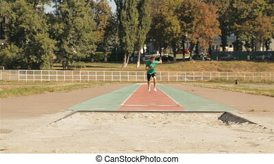 Male athlet practices long jumping at the stadium