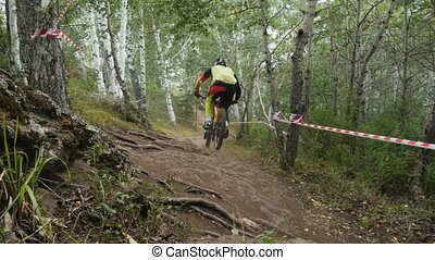 male athlete competitor downhill rides in forest