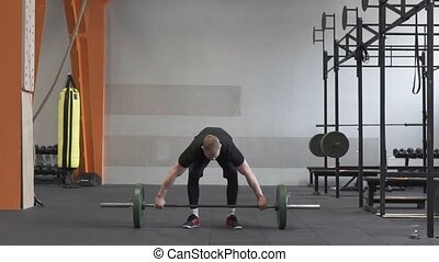 Male athlete doing barbell snatch exercise in cross fit gym
