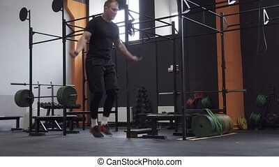Male athlete doing double jumps rope in cross fit gym