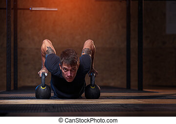 Male athlete doing push up with kettle bells