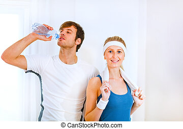 Male athlete drinking water from bottle and smiling girl in sportswear with towel