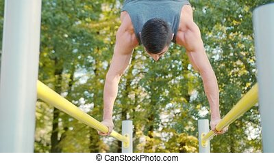 Male Athlete Exercise on Gymnastic Parallel Bars - Male...
