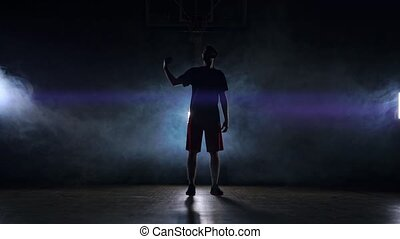 Male athlete in sportswear and sneakers throws a basketball...