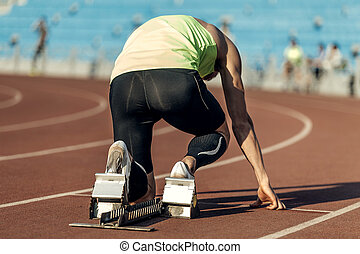 male athlete in starting blocks