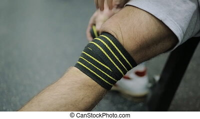 male athlete in the sport shoes 30 years of age rewinds his knee on the leg hair sport athletic bandage black with yellow stripes, for Security, to load on the joint.