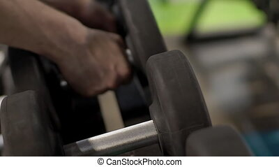 Male athlete is taking dumbbells in hands in modern gym indoors.