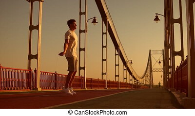 male athlete jumps at the bridge - man doing jump rope...