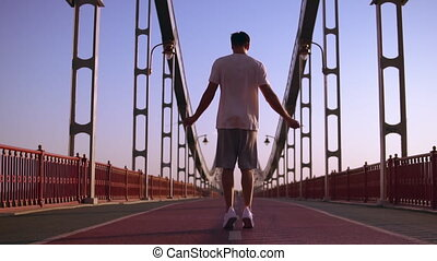 male athlete jumps on the bridge - man working out outdoors....