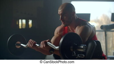 male athlete lifts a barbell with weight sitting on a bench. Slow motion exercise of the hands