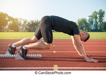 Male athlete on starting position at athletics running track.