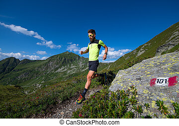 Male athlete practicing mountain running on a trail downhill