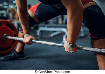 Male athlete prepares to pull the barbell