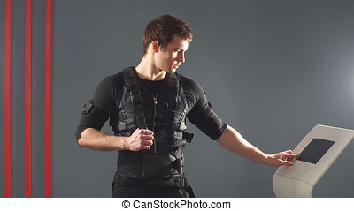 Male athlete pushing on screen on ems machine regulating...