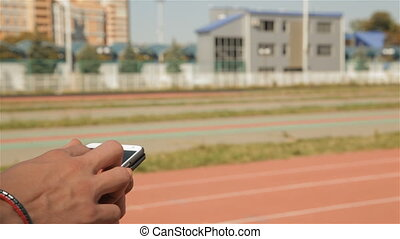 Male athlete run on time at the stadium
