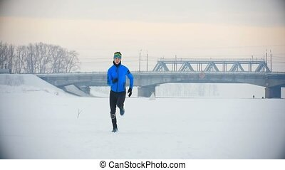 Male athlete running fast in winter ice field, sport and...