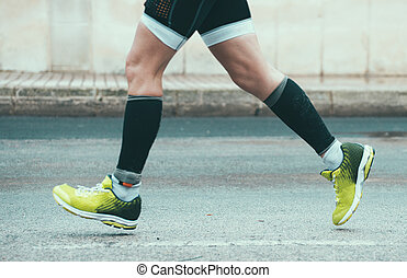 Male athlete running on the street.