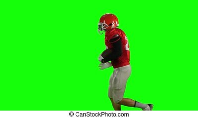 Male athlete runs with the ball in his hands. Green screen
