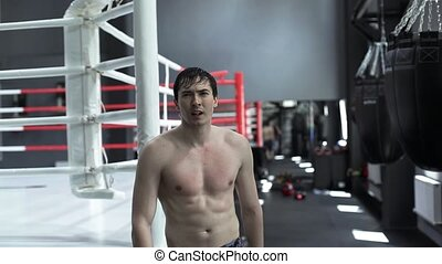 Male athlete walking alone in boxing gym