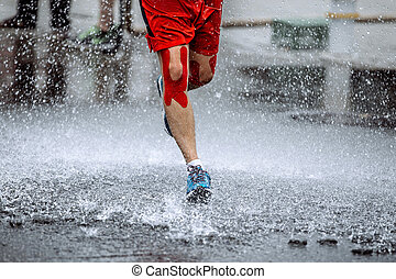 male athlete with tape on his knees running through a puddle...