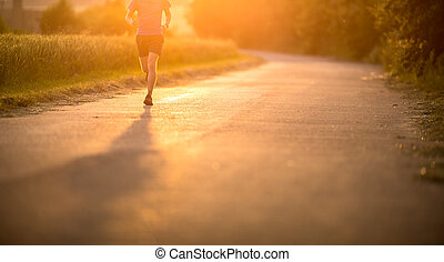 Male athlete/runner running on road - jog workout well-being concept