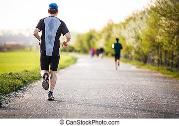 Male athlete/runner running on road
