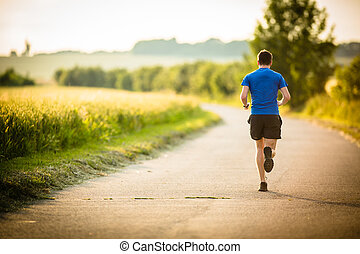 Male athlete/runner running on road