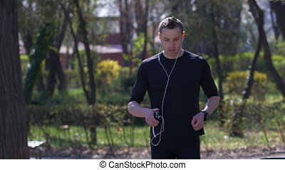 Male athletic jogger stops running to setting up smartwatch counter and checking his smartphone
