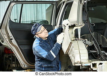 Young auto mechanic worker repair flatten and align metal car body in automotive industry