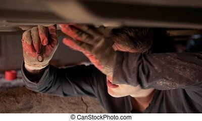 Male auto mechanic underneath a car screwing components in the garage