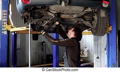 Male auto mechanic working under car in garage