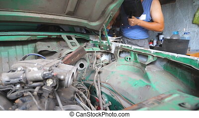 Male automaster welds metal parts of old car with...