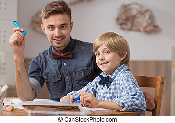 Male babysitter with boy drawing