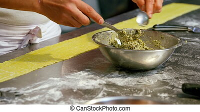 Male baker putting ingredients on pasta dough 4k - Male ...