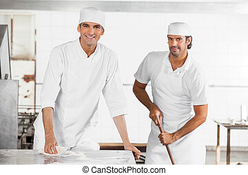 Male Baker's Smiling While Cleaning Bakery