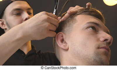 Male barber combing and cutting hair of young customer by...