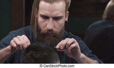 Male barber cutting hair of man in Barbershop