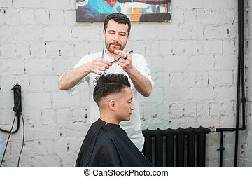 Male Barber Giving Client Haircut In Shop