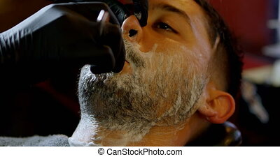 Male barber shaving a clients beard 4k - Male barber shaving...