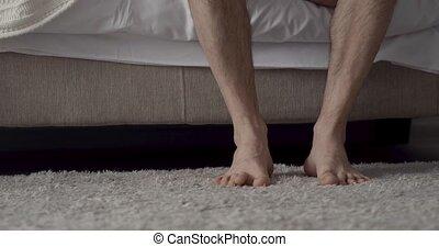 male bare feet photo - Man putting on feet on the carpet....