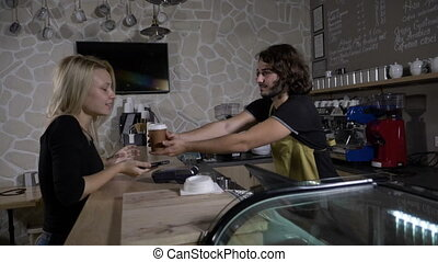 Male barista serves and flirts with a beautiful female customer who pays using smartphone app in a coffee shop in slow motion