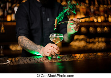 Male bartender adding to a cocktail glass with dried orange a smoked cinnamon with tweezers