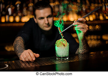 Male bartender adding to a glass with dried orange and crushed ice a smoked cinnamon with tweezers