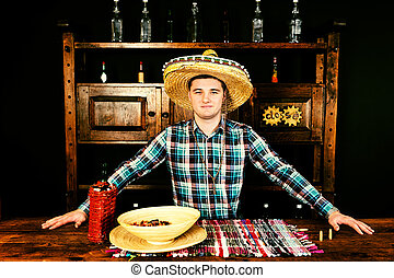 Male bartender in a sombrero standing at the counter, bottle of tequila and a plate with snacks on it