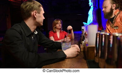 Male bartender talking with customers at bar counter - Male...