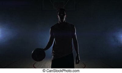 Male basketball player moving in the smoke at the camera...