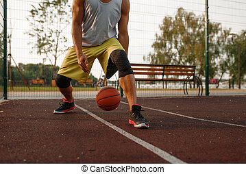 Male basketball player with ball shows his skill