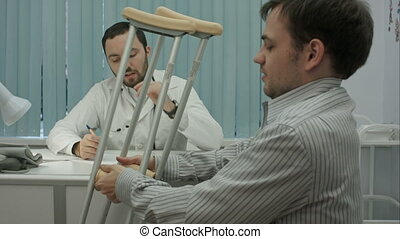 Male bearded doctor in clinic consult sick client with crutches.
