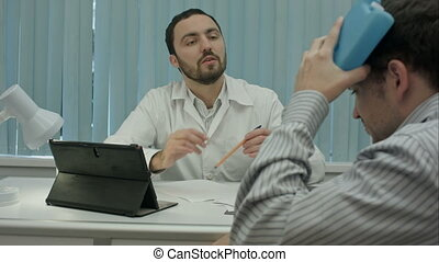 Male bearded doctor in clinic consult sick client with head injury.