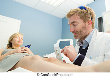 male beautician pointing out an area on the leg